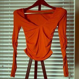 Long sleeve tight orange top.
